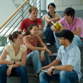 A group of young people are sitting on some stairs having a conversation.